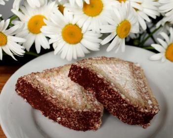 два кусочка торта из печенья и начинки на белой плоской тарелке на столе, рядом ромашки