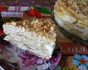 кусок торта наполеон, смазанного кремом, на тарелке на столе, покрытом скатертью