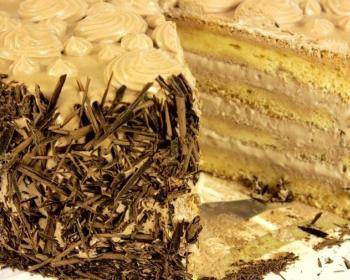 разрезанный бисквитный торт с кремом и шоколадной стружкой