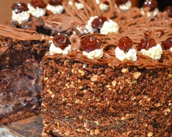разрезанный торт с пьяной вишней, орехами и кремом
