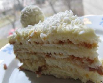 кусочек бисквитного торта Рафаэлло, присыпанного кокосовой стружкой, сверху лежит шарик в кокосовой стружке