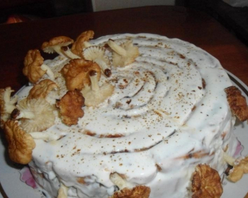 торт с курагой и черносливом, политый кремом и украшенный печеными грибочками, на тарелке на столе