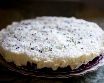 торт с вишней и маскарпоне, присыпанный кокосовой стружкой, на плоской тарелке на столе