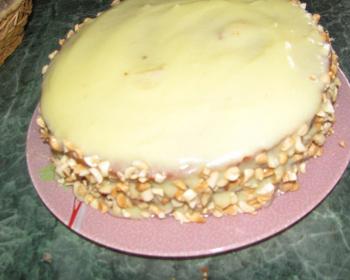 торт спартак из коржей, смазанных кремом и посыпанных орехами, на тарелке на столе