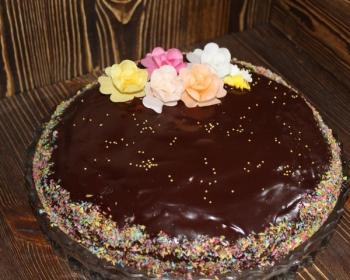 торт в шоколадной глазури с вареньем, украшенный присыпкой и кремом