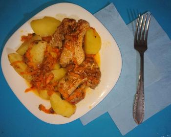 порция тушеной картошки с ребрышками в тарелке на столе