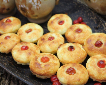 творожные капкейки с ягодами калины в черной тарелке на столе