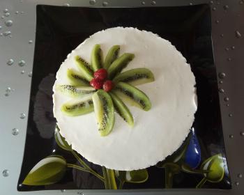 творожный десерт с желатином, украшенный дольками киви и ягодами, в плоской тарелке на кухонном столе