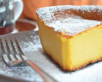 треугольный кусок тыквенного кекса, присыпанный сахарной пудрой, на серой тарелке, рядом вилка