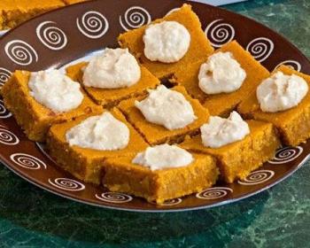 на коричневой тарелке лежит тыквенный пирог, разрезанный квадратиками, сверху на каждом кусочке лежит белый крем