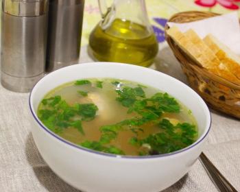 уха из кусочков красной рыбы и зелени в белой тарелке на столе, рядом ложка и ломтики белого хлеба в корзине