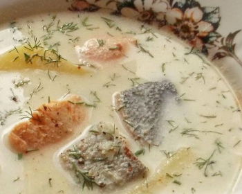 финская сливочная уха с кусочками красной рыбы, картофелем и рубленым укропом в тарелке