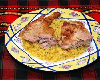 запеченные кусочки утки с рисом и яблоками на плоской тарелке на столе, застеленном пледом