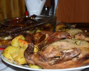 запеченные кусочки мяса утки с картофелем на тарелке на столе