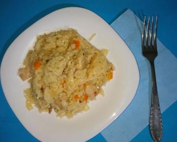 узбекский плов с куриным мясом в белой тарелке на столе, рядом вилка