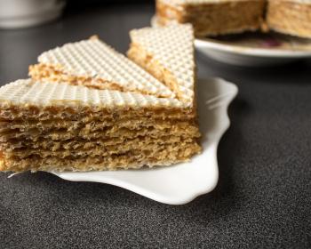 три кусочка вафельного торта на небольшом белом блюдце на столе