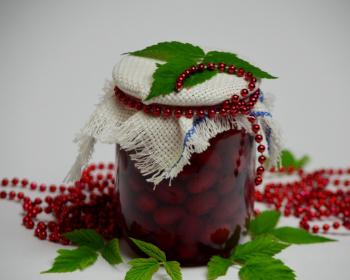 варенье из кизила с ягодами в закрытой стеклянной банке на столе, рядом зеленые листики и красные бусы
