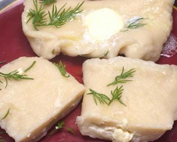 вареники с яйцом Тухум барак в тарелке со сливочным маслом и свежим укропом