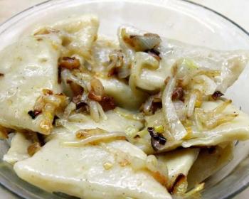 вареники с капустой в тарелке в сопровождении жареного лука и сала