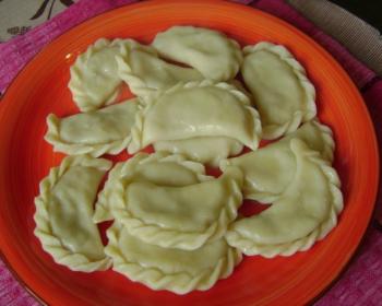 отварные вареники с картошкой и грибами на красной тарелке