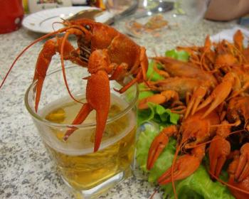 вареный рак на бокале с пивом, рядом большая тарелка с вареными раками