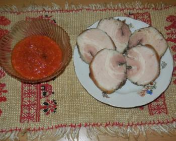 кусочки вареного рулета из сала на белой тарелке на столе, покрытом скатертью, рядом пиала с красным соусом
