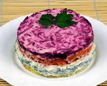 вегетарианская шуба со сметаной, оформленная в виде круга, лежит на белой круглой тарелке, сверху лежит веточка петрушки