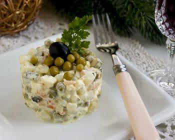на квадратной тарелке лежит порция вегетарианского оливье с сыром и сметаной, сверху на салате лежит консервированный горошек, маслина и веточка петрушки