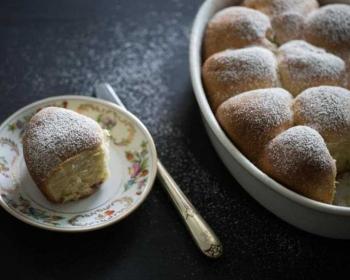 пышные венские булочки в емкости для запекания, присыпанные сахарной пудрой, рядом на столе стоит блюдце с булочкой, рядом с блюдцем обеденный нож