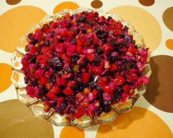винегрет из свеклы, картофеля, лука, капусты и зеленого горошка в стеклянной тарелке на столе