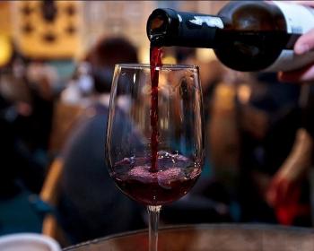 вино из черноплодной рябины в стеклянном бокале на столе