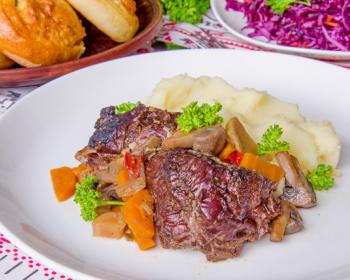 мясо зайца с грибами, морковью, картофельным пюре и зеленью на тарелке
