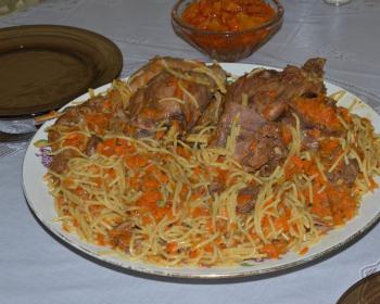 тушеные кусочки зайчатины с вермишелью и морковью на белой тарелке на столе, застеленном скатертью
