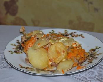 запеченные кусочки зайчатины с картошкой и морковью на белой тарелке на столе, застеленном скатертью