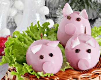 в плетеной корзиночке на листе салата лежат три куриных яйца розового цвета в виде свинок
