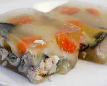 две порции заливной рыбы с кусочками моркови на белой тарелке