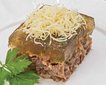 квадратный кусочек заливного из говядины на белой тарелке, сверху лежит измельченный хрен, рядом лежит веточка петрушки