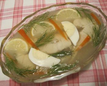 заливное из кусочков судака с вареными яйцами, ломтиками лимона и веточками укропа в стеклянной салатнице на столе