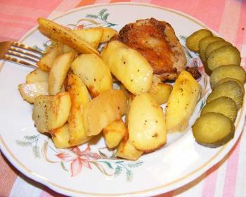 запеченная курица с картошкой в тарелке с нарезанными кружочками солеными огурцами