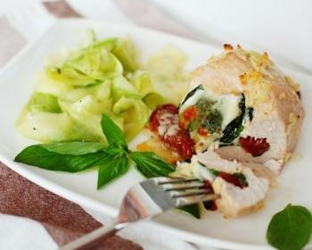 запеченное филе индейки с сыром и вялеными томатами внутри в разрезе на тарелке с овощным гарниром