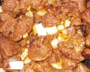 жареные кусочки мяса косули, перемешанные с нарезанным репчатым луком, в сковороде