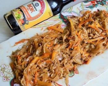 жареная квашеная капуста на белой тарелке на столе, рядом бутылка соевого соуса