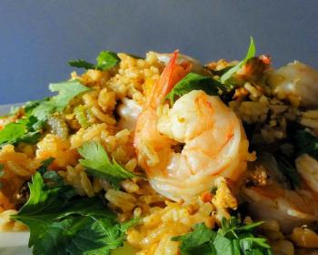 жареный рис по-тайски с креветками, яйцом и овощами, украшенный зеленью, в тарелке на столе