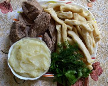 жижиг-галнаш из кусочков говядины, с вареными полосками теста, картофельным пюре и веточками укропа с петрушкой на белой тарелке на столе, застеленном скатертью