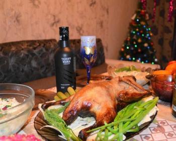 утка по-пекински на праздничном новогоднем столе на фоне елки