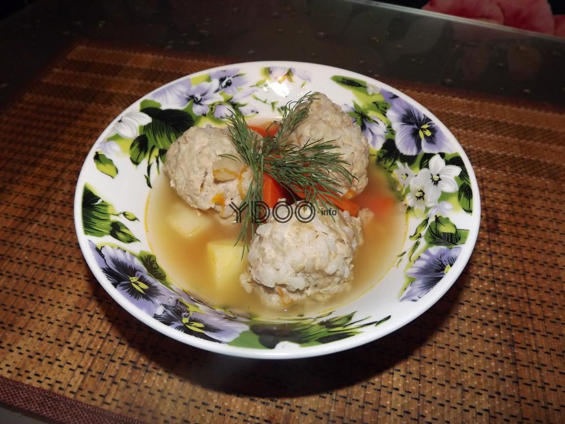 три фрикадельки с рисом в овощной подливке в тарелке на кухонном столе