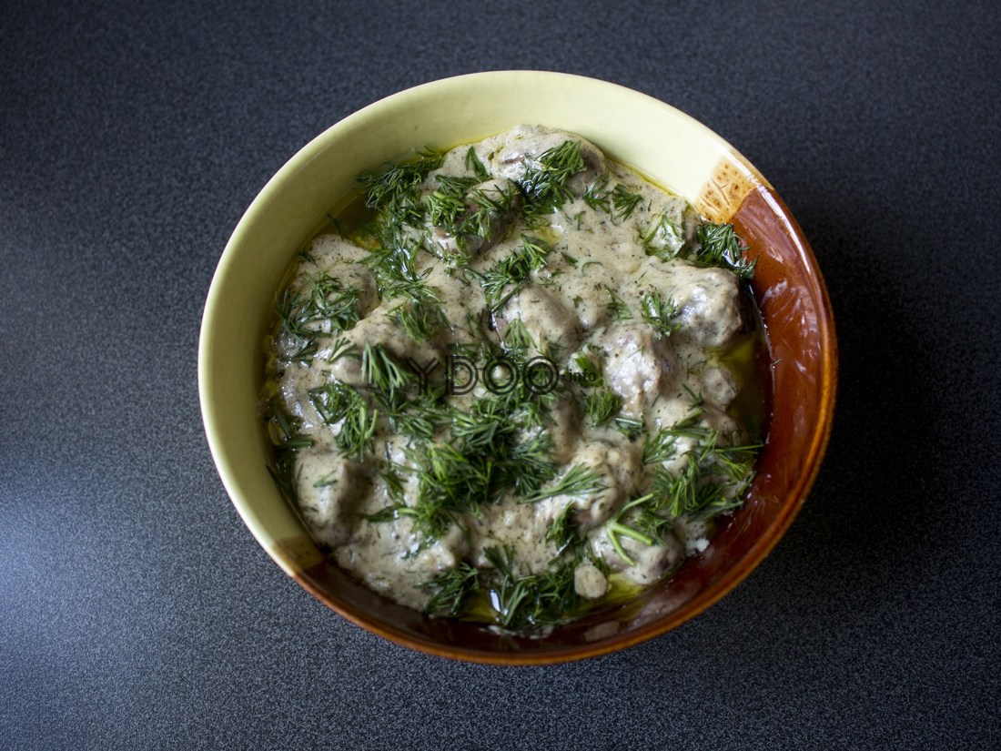 тарелка с тушеными в сметане куриными сердечками, посыпанными свежей измельченной зеленью укропа