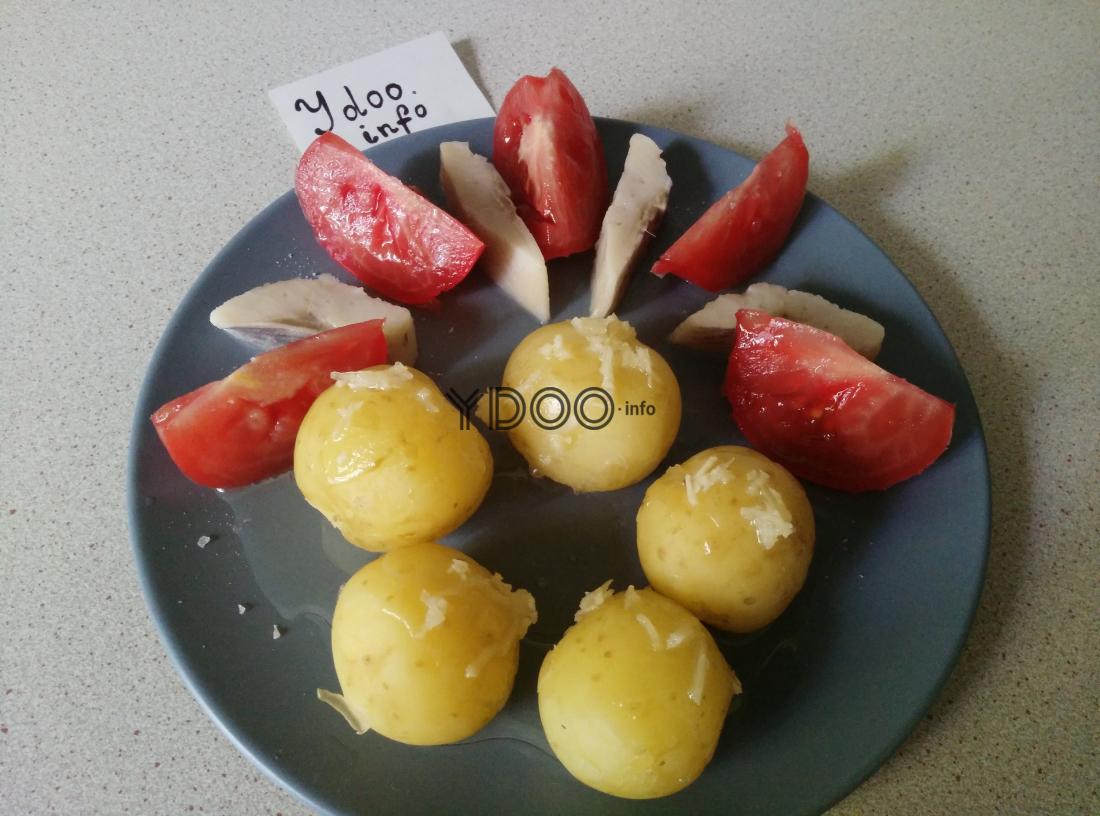 вареный молодой картофель, заправленный чесноком, в тарелке с селедкой и помидорами