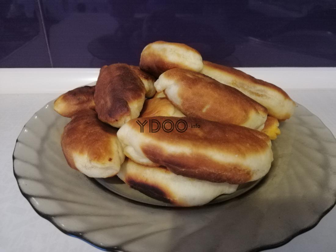 горка жареных пирожков с капустой и мясом в тарелке на кухонном столе