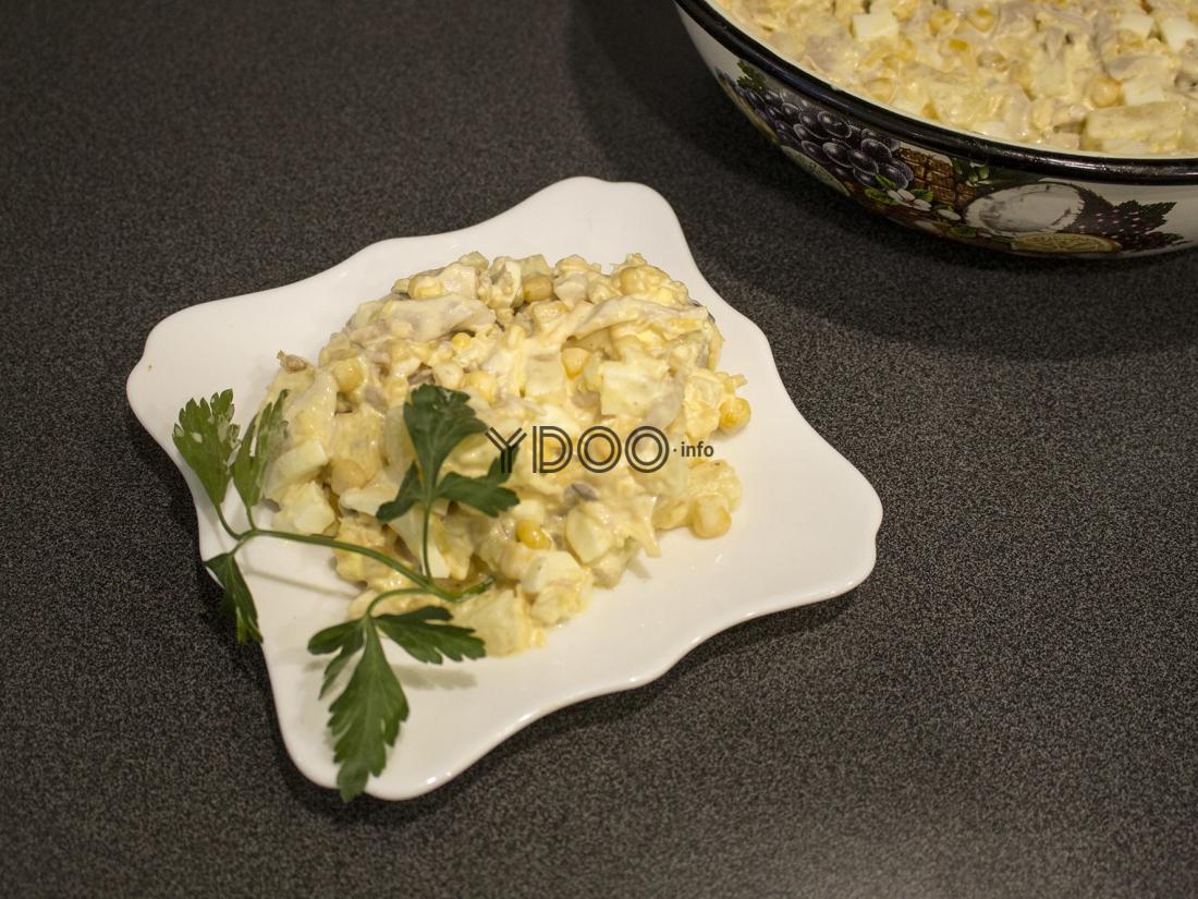 салат Дамский каприз, украшенный листиками свежей петрушки, в белой резной тарелке на столе